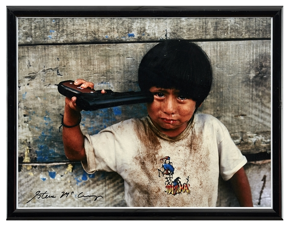 McCurry Steve | Young boy holding toy gun to his head